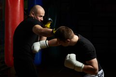 Boxing combat between two young man. Boxing combat between two young men on modern gym background royalty free stock photography