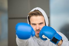 Boxing concept. Man athlete on concentrated face with sport gloves practicing boxing punch, urban background. Boxer with. Hood on head practices jab punch royalty free stock images