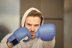 Boxing concept. Man athlete on concentrated face with sport gloves practicing boxing punch, urban background. Boxer with. Hood on head practices jab punch stock photo