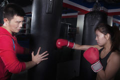 Boxing couch holding the punching bag and training a female student Royalty Free Stock Photography