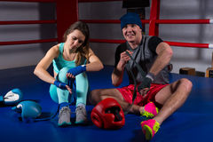 Boxing couple preparing bandages for fight near lying boxing gloves and helmet. In regular boxing ring in a gym stock image