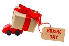 The BOXING DAY concept. Red toy car delivering gifts box with ta stock photos