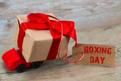 The BOXING DAY concept. Red toy car delivering gifts box with ta stock photography