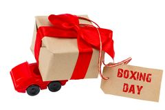 The BOXING DAY concept. Red toy car delivering gifts box with ta royalty free stock images