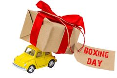 Boxing Day concept. Yellow retro toy car delivering gifts box wi royalty free stock image