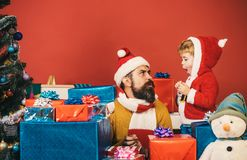 Boxing day and family concept. Santa and little assistant. Among gift boxes near Christmas tree. Christmas family opens presents on dark red background. Man royalty free stock photo