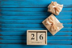 Boxing day sale. Wooden calendar and gift boxes with bows on blue shabby wooden background.Copy space for text Royalty Free Stock Images