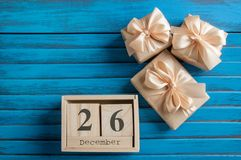 Boxing day sale. Wooden calendar and gift boxes with bows on blue shabby wooden background.Copy space for text Royalty Free Stock Image