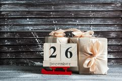 Boxing day sale. Wooden calendar and gift boxes with bows on brown shabby wooden background Stock Images