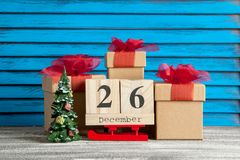 Boxing day sale. Wooden calendar and gift boxes  with red bows on blue shabby wooden background Royalty Free Stock Image