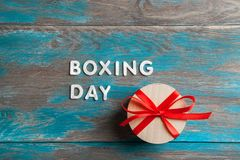 Boxing day sale. And gift box with red bow on blue shabby wooden background Stock Photo