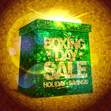 Boxing day sale with shiny gift box against gold mosaic backdrop. Stock Photos