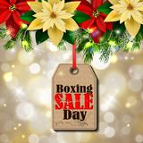 Boxing day tag. Boxing day sale tag with evergreen trees with poinsettia christmas lights isolated on bokeh background Royalty Free Stock Photo