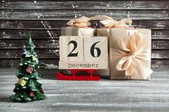 Boxing day sale. Wooden calendar and gift boxes with bows on brown shabby wooden background Stock Image