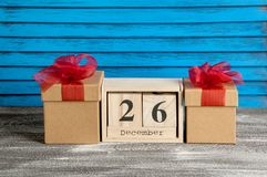 Boxing day sale. Wooden calendar and gift boxes with red bows on blue shabby wooden background Stock Image