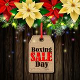 Boxing day tag. Boxing day sale tag with evergreen trees with poinsettia christmas lights isolated on wooden wall Royalty Free Stock Images