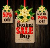 Boxing day tag. Boxing day sale tags with evergreen trees with christmas bells isolated on wooden wall Stock Images