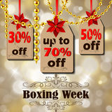 Boxing day tag. Boxing week sale tags with poinsettia christmas lights isolated on bokeh background golden beads Royalty Free Stock Photo