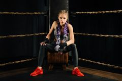 Boxing fashion girl on break sits on a chair resting in a boxing competition ring. Sexy amazing female model. Beautiful braiding kanekalon pigtails hairstyle Stock Photography