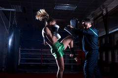Boxing girl doing knee kick Royalty Free Stock Image