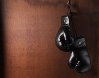 Boxing-glove. Hanging on grunge wooden background Royalty Free Stock Photo