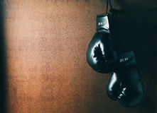 Boxing-glove. Hanging on grunge wooden background.toned image Royalty Free Stock Photography