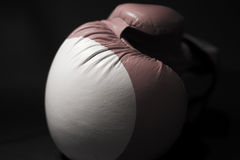 Boxing glove. Red and white boxing glove on a black background Stock Photos