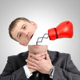 Boxing glove beating from businessmans head. On grey background, close up view Royalty Free Stock Photo
