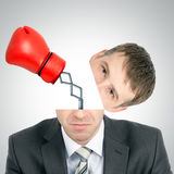 Boxing glove beating from businessmans head. On grey background, front view Stock Photos
