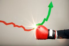Economic crisis and success concept. Boxing glove punching red downward arrow and turning into a green rising one on light background. Economic crisis and Stock Photos