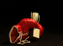 Boxing glove and a shining cup. Dark background and a red left-hand boxing glove holding a winner-cup royalty free stock image