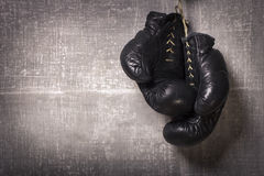 Boxing Gloves. Old boxing gloves hanging on a grungy background Royalty Free Stock Images
