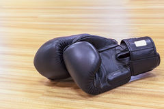 Boxing gloves black color on wooden floor Royalty Free Stock Images