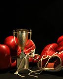 Boxing gloves and a golden cup. Golden winner-cup between two red boxing gloves, in front of a dark background Stock Photo