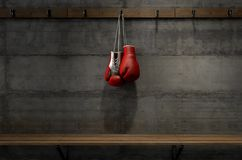 Boxing Gloves Hanging In Change Room. Spotlit boxing gloves hanging on a hanger above an empty wooden bench in a locker change room - 3D render stock photography