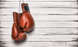 Boxing gloves hanging on wooden wall Stock Photos