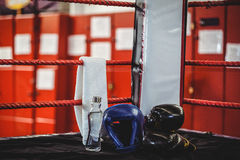 Boxing gloves, headgear, water bottle and a towel in boxing ring Royalty Free Stock Photo