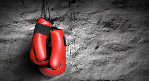 Boxing gloves. Pair of red boxing gloves hanging on wall Stock Photos