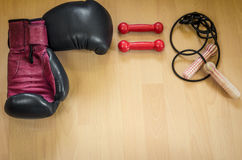 Boxing gloves, red dumbbells and skipping rope Stock Photos