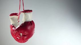 Boxing gloves rotation. Boxing gloves hanging and rotating on gray background
