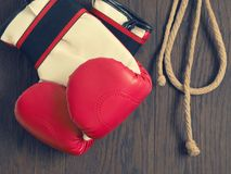Boxing gloves on wood. Red boxing gloves on a rustic wooden wall, sports or assertiveness concept stock photography