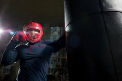 Boxing in gym. Young athlete in boxing helmet and gloves kicking punching bag in gym Royalty Free Stock Photos