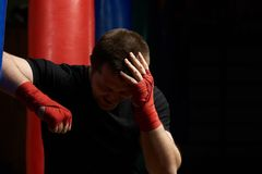 Boxing man holding head in pain. After injury. Head  injury theme Royalty Free Stock Photos