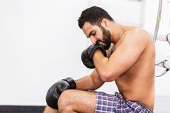 The Boxing Man. Muscular handsome topless boxer wears black gloves sitting near the ring stock photos