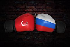 A boxing match between. A boxing match. Confrontation between the Turkey and Russia. Russian and Turkish national flags on Boxing gloves. Sports competition Royalty Free Stock Image