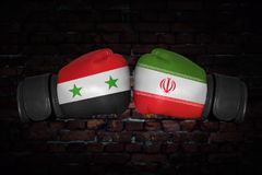 A boxing match between the two countries. A boxing match. Confrontation between the Iran and Syria. Syrian and Iranan national flags on Boxing gloves. Sports Stock Photo