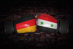 A boxing match between the two countries. A boxing match. Confrontation between the Germany and Syria. Syrian and German national flags on Boxing gloves. Sports Royalty Free Stock Image