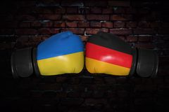A boxing match between the two countries. A boxing match. Confrontation between the Ukraine and Germany. German and Ukrainian national flags on Boxing gloves Royalty Free Stock Photography