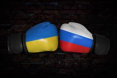 A boxing match between the Ukraine and Russia. Boxing match. Confrontation between the Ukraine and Russia. Russian and Ukrainian national flags on Boxing gloves Royalty Free Stock Photography