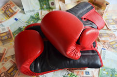Boxing and money. Boxing gloves on euro banknotes of different denomination Royalty Free Stock Images